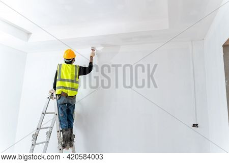 Asian Painter Man Painting The Wall In An Unfinished Building, With Paint Brush And Bucket, Isolated