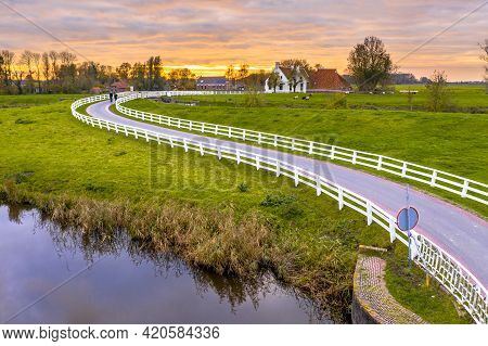 Aerial Scene Of Dutch Countryside Landscape With Historical Houses In Evening Along A Curved Road Wi
