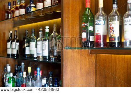 Soft Focus Shot Of Wooden Shelf In A Bar Pub Hotel Filled With Liqor Bottles From Top Brands Of Whis
