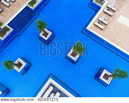 Aerial View Of Luxury Outdoor Swimming Pool And Deck-chairs.