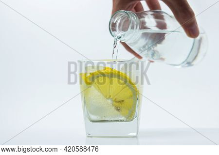 Lemon With Ice In A Glass. Refreshing Drink With Lemon. Water Is Poured Into A Glass With Ice.