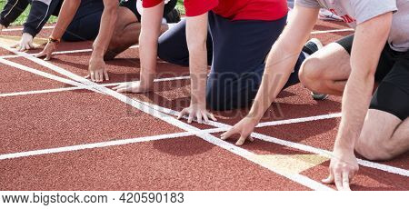 High School Boys Track And Field Runners At The Starting Line Ready To Start A Sprint Race In Lanes