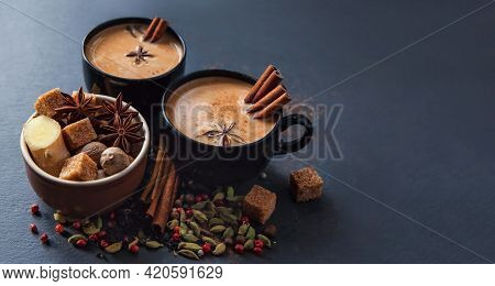 Masala Tea Traditional Hot Indian Spiced Drink In Black Cups. Spices Cinnamon Sticks, Cardamom Pods,