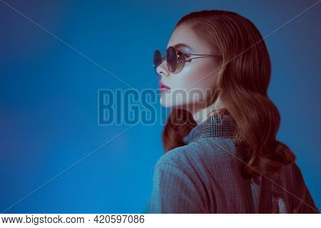 Portrait of a beautiful fashionable young woman in modern round sunglasses. Glasses fashion.