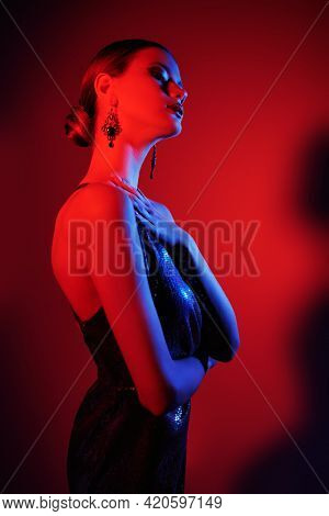 Evening fashion, makeup and hairstyle. Portrait of a beautiful graceful girl posing in elegant evening dress in red light. Studio shot.