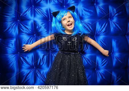 Carnival costume. Portrait of a cute little girl child in cat costume and bright blue wig laughing at camera. Halloween party.