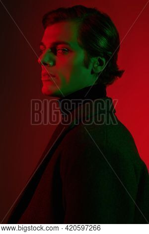 Portrait of a serious handsome man in elegant clothes posing at studio in red and green light. Men's beauty. Fashion.