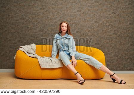Fashion shot. Beautiful fashion model girl poses in denim jumpsuit on a bright yellow sofa in a modern apartment. Modern interior, furniture.