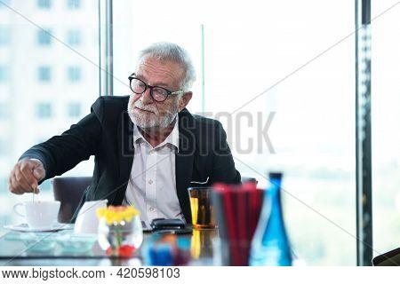 Business Partner Executive Smart Man Sitting Drinking Coffee In Restaurant. Senior Caucasian Man Wai