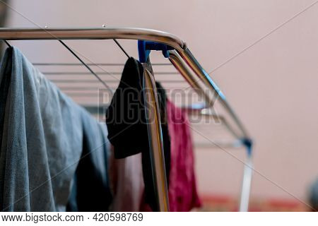 Clothes Hangs On A Folding Drying Rack In The Room. Collapsible. Drier. Apartment. Housekeeping. Wet