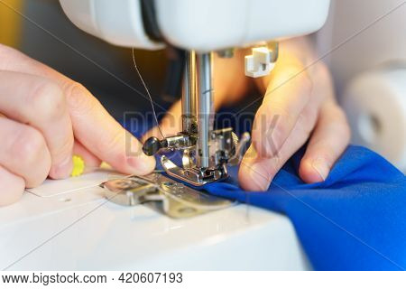 Close Up Shot Of Tailor Or Seamstress Sewing Or Stitching Blue Navy Fabric With Professional Machine