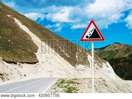 International traffic sign 'Falling rock' standing on highway road. North Caucasus, Republic of Ingushetia, Russia