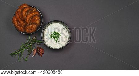 Arial View Of Crispy Baked Sweet Potato Chips Garnished With Chili, Rosemary And Thyme And Yogurt Ga