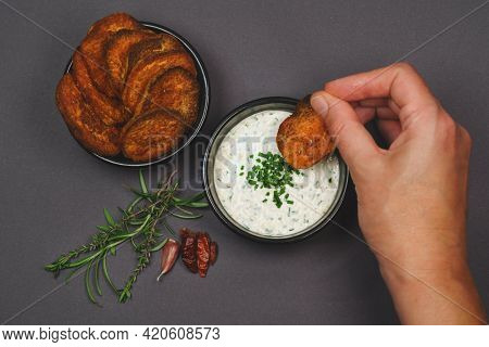 Arial View Eating Spicy Sweet Potato Chips Garnished With Chili, Rosemary And Thyme And Yogurt Garli