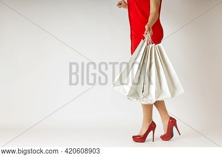 A Slender Girl In A Red Dress And Red Shoes Coquettishly Carries Bags With New Things In Her Hand. T