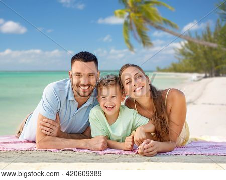 family, travel and tourism concept - happy mother, father and little son lying on blanket over tropical beach background in french polynesia