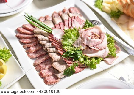 Sliced Meat Is Decorated With Greens. Banquet Table With Delicious Food In A Restaurant. Professiona