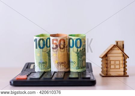 Rolled Up Paper Money In Denominations Of 100 And 50 Euros, On A Calculator, Against The Background