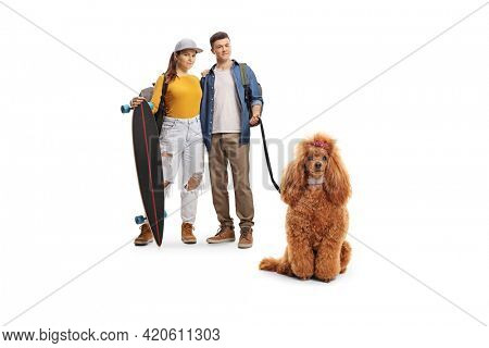 Young couple with backpacks and a longboard with a red poodle dog on a lead isolated on white background
