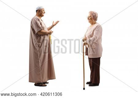Full length profile shot of a mature muslim man talking to an elderly woman with a walking cane isolated on white background