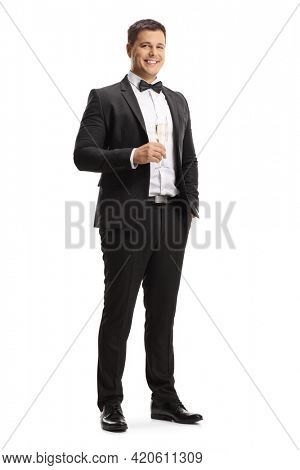 Elegant young man in a suit and bow tie holding a glass of sparkling wine isolated on white background
