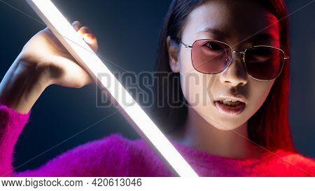 Color Light Face. Cyberpunk Beauty. Eyewear Fashion. Neon Portrait Of Glamour Asian Girl In Pink In
