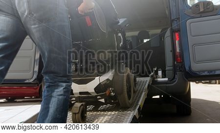 Assistant Helping Disabled Person On Wheelchair With Transport Using Accessible Vehicle Ramp