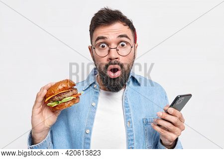 Hungry Bearded Adult Man Eats Delicious Burger Holds Mobile Phone Finds Out Shocking News Wears Roun