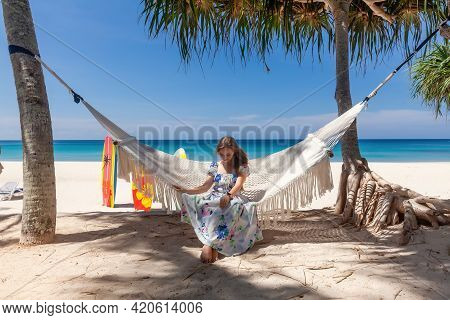 Travel Woman In Dress Sitting On White Hammock On Sandy Beach With Blue Sea And Tropical Trees. Fema