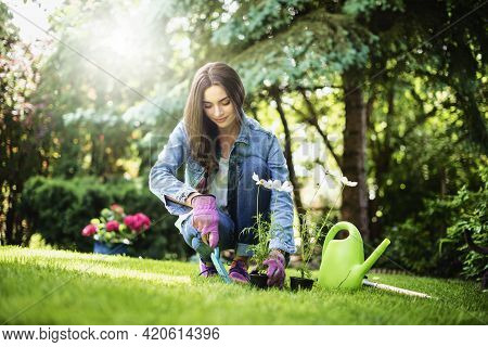 Happy Young Woman Planting Flowers In The Garden