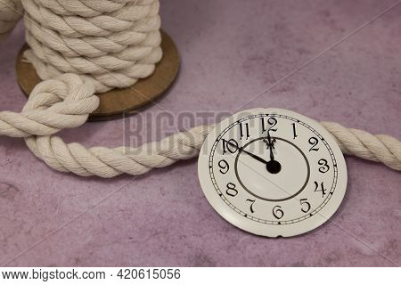 Watch Dial And Old Rope On A Reel On A Pink Solid Background
