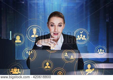 Attractive Businesswoman Using Laptop To Find New Candidate Using Alumni Network. Social Media Icons