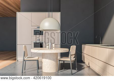 Dark And Wooden Beige Kitchen Set With Concrete Round Table And Two Beige Chairs On Grey Floor. Mini