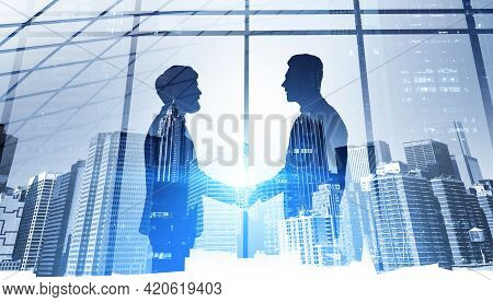 Businessmen Shake Hands, Silhouettes Of Two People. Double Exposure Of City Buildings, Downtown. Con