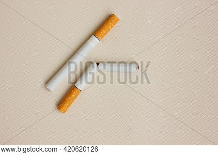 Two Cigarettes With A Yellow Filter On A White Background. One Cigarette Is Whole, The Other Is Brok
