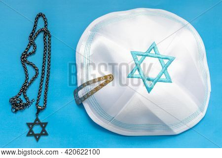 Jewish Kippah With Embroidered Blue David Star Alongside A Star Of David Necklace