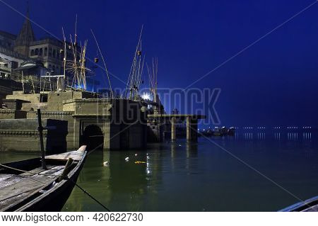 Night Wide Angle View Of Ghat Located Next To Ganga River With Temple And Boats In Varanasi, India I