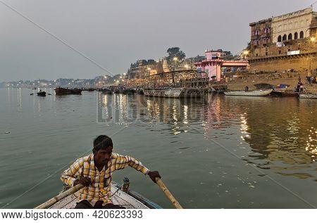 Varanasi, India - November 01, 2016: A Man Rowing A Wooden Boat Over River Ganga With Bamboo Paddles