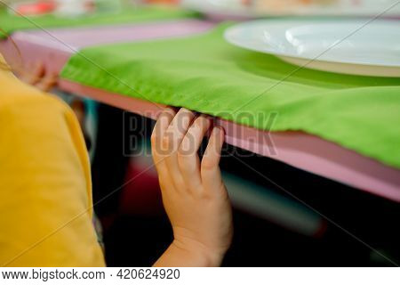 Children's Hand Touching The Table On The Restaurant. Waiting For The Meal. Green Napkin Under A Whi