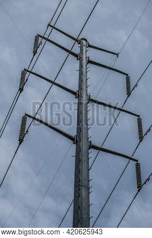 Looking Upwards To The Top Portion Of A Tower That Supplies Electricity With Cable Attached To The I