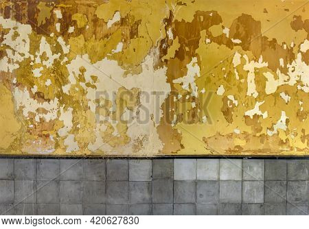 Peeling Paint Texture. Grunge Wall Background With Cracked And Peeled Yellow Paint And Grey Tiles
