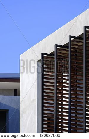 Low Angle View Of Folding Metal Sunshade Battens On Loft Cement Wall Of Modern Building Against Blue