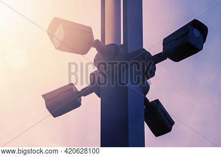 Video Surveillance System On Pole In City Park On The Background Sky, Monitoring The Situation With