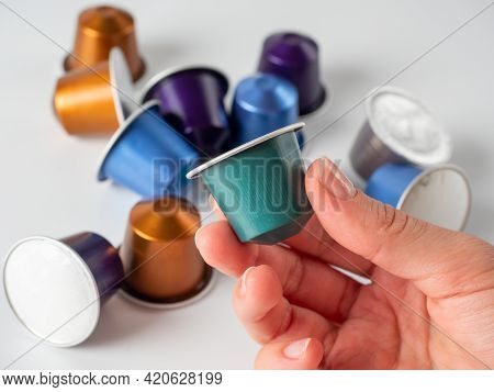 Colored Aluminum Capsule With Ground Coffee In Hand. White Background With Other Capsules Lying On I