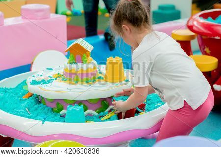 Unrecognisable Little Girl In White T-shirt And Pink Pants Playing Blue Kinetic Sand On The Indoor P
