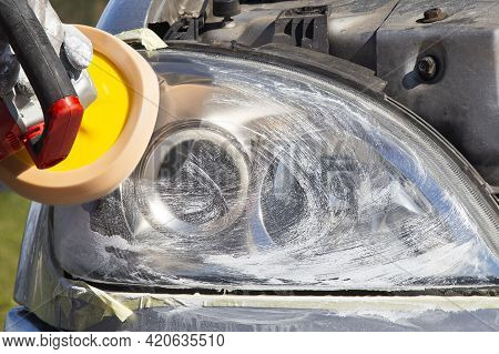 Polishing The Front Light Of The Car With Polishing Machine