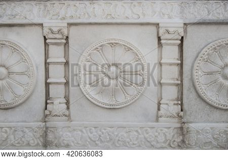 Details of stone carving work on the white marble. Flower shape motif carved on the white marble on the wall of a temple.