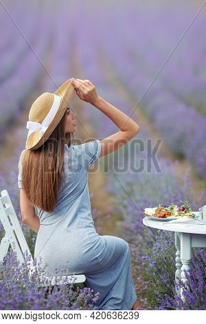 Back View Of Young Woman Wearing Straw Hat And Dress Sitting At Table Served With Croissants, Orange