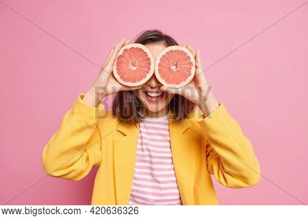 Vitamins For Skin Care And Beauty. Positive Dark Haired Young Woman Covers Eyes With Grapefruit Halv