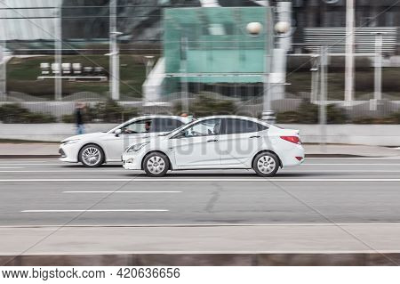 Two White Cars Are Moving Along The Street At High Speed. Speeding In The City Concept. Compliance W